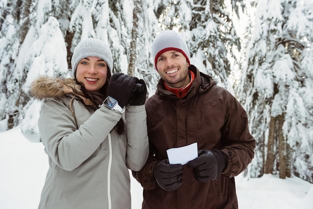 Casal de esquiadores segurando um binóculo e um cartão de endereço em uma montanha coberta de neve