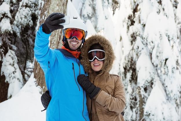 Casal de esquiadores tirando uma selfie em paisagem de neve