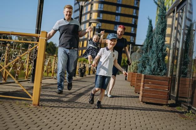Casal de família caucasiano andando com menina levantando bebê por mãos mulher está feliz rindo menino r ...