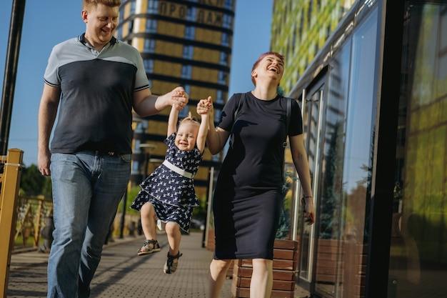 Casal de família caucasiano caminhando com uma menina levantando um bebê com as mãos. mulher está rindo alegremente