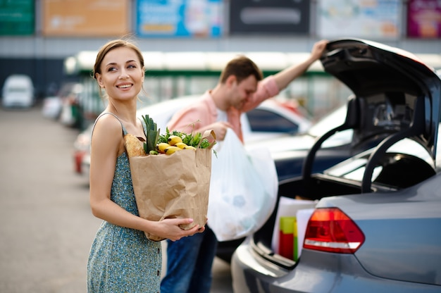 Casal de família coloca suas compras no porta-malas