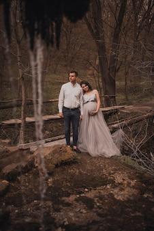 Casal de família com uma mulher grávida com uma grande barriga na natureza