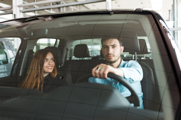 Casal de família em seu carro novo na concessionária
