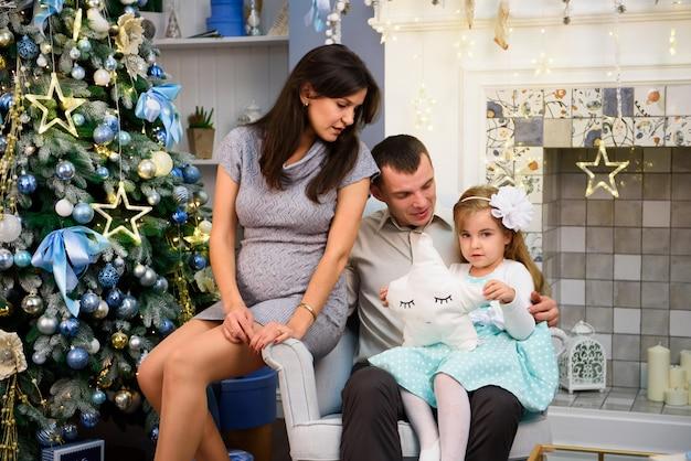 Casal de família feliz dá presentes na sala de estar, atrás da árvore de natal decorada, a luz dá uma atmosfera acolhedora.