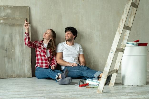 Casal de família feliz relaxando depois de pintar um jovem casal deitado no chão de uma casa nova e se comunicando