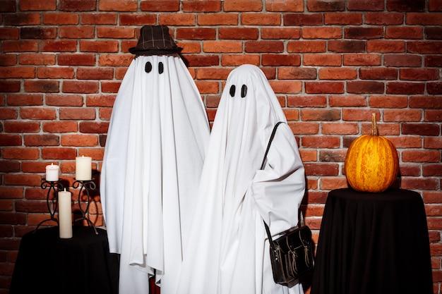 Casal de fantasmas posando sobre parede de tijolo, festa de halloween.