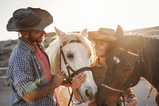 Casal de fazendeiros se divertindo com cavalos sem bits durante o dia de sol dentro do curral do rancho - foco no olho do animal central
