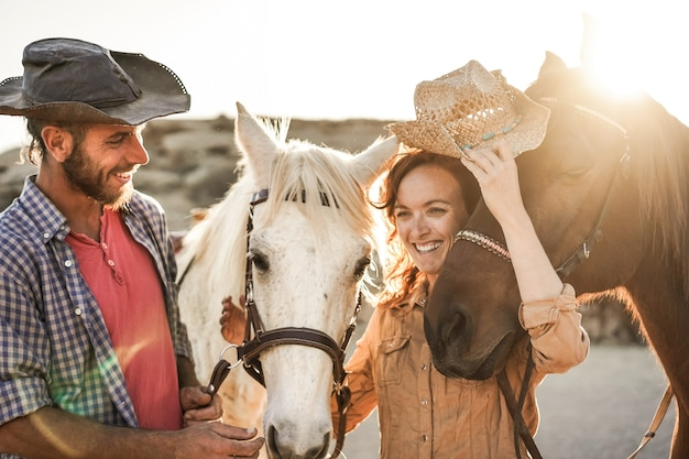 Casal de fazendeiros se divertindo com cavalos sem bits durante o dia de sol dentro do curral do rancho - foco principal no cavalo certo