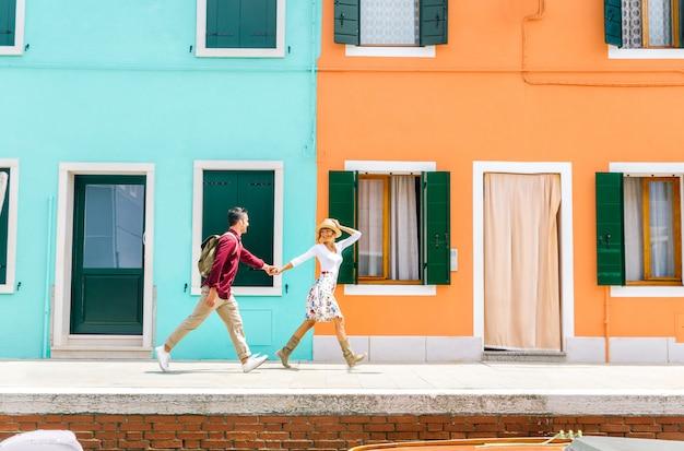 Casal de férias em veneza, itália. homem e mulher apaixonada, andando na cidade de burano, na frente de edifícios coloridos.