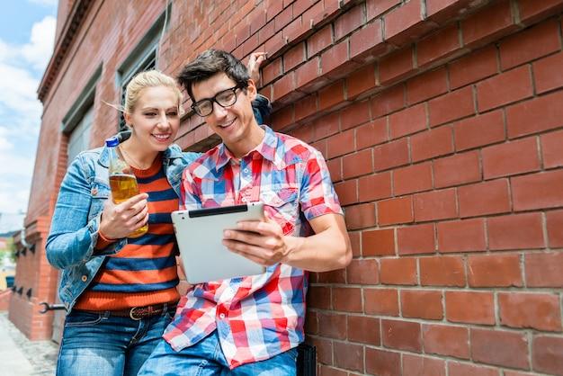 Casal de férias organizando passeios turísticos com tablet pc