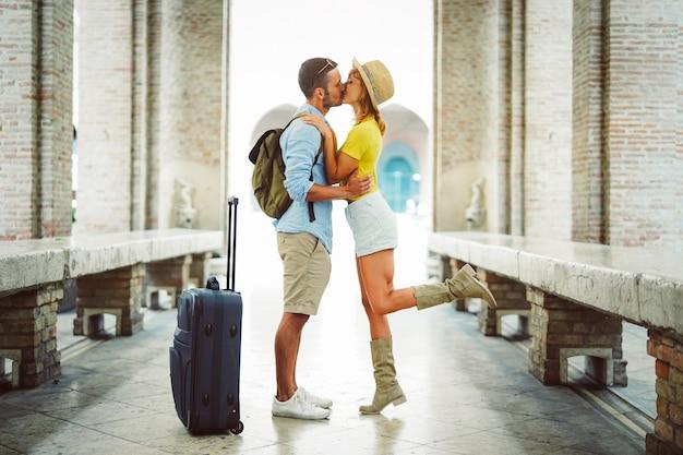 Casal de férias, tendo um beijo romântico na rua na cidade.