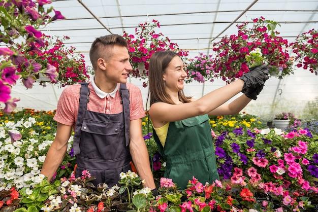 Casal de floristas cuidando de flores em estufa industrial