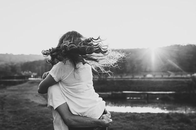 Casal de foto abraçando, marido e mulher perto do lago. fechar-se. verão. retrato de um jovem romântico e uma mulher apaixonada na natureza. marido e mulher na luz solar. foto em preto e branco.