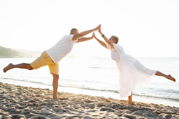 Casal de fotos completas posando na praia