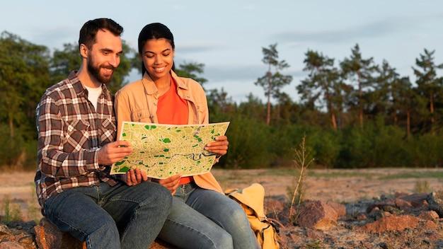Casal de frente olhando juntos em um mapa