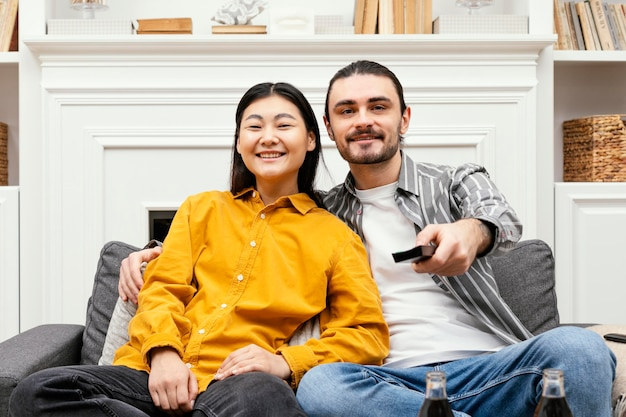Casal de frente para o sofá sentado no sofá assistindo tv