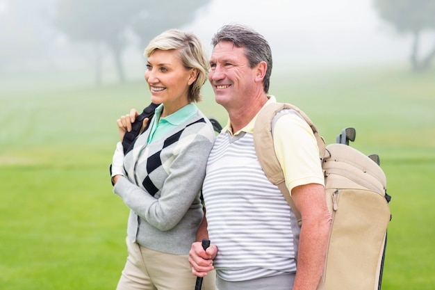 Casal de golfe sorrindo e segurando clubes