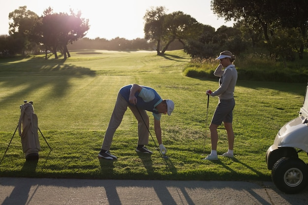 Casal de golfe teeing fora para o dia em uma manhã ensolarada no campo de golfe