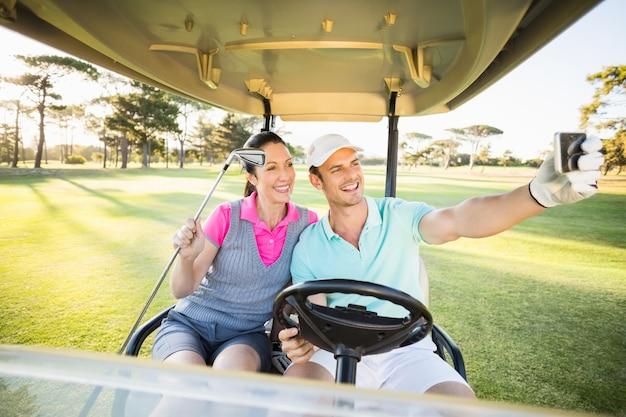 Casal de golfista sorridente tendo auto-retrato
