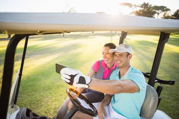 Casal de golfista sorridente tomando selfie