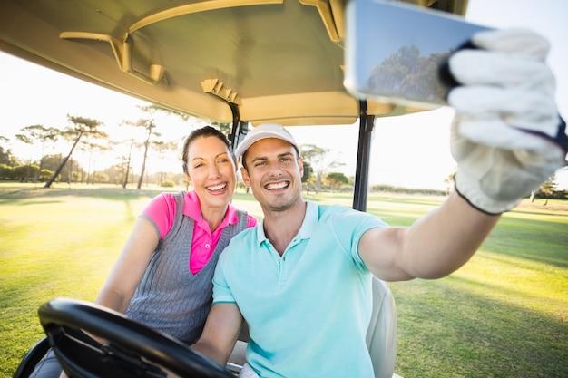 Casal de golfista tomando selfie enquanto está sentado no carrinho de golfe