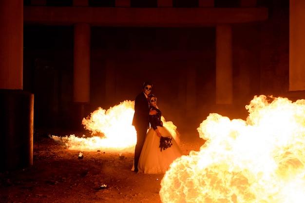 Casal de halloween em pé com lança-chamas. grande incêndio