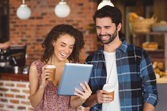 Casal de hipster sorridente com copos take-away, usando o tablet