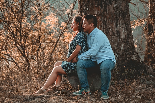 Casal de homem e mulher grávida na natureza