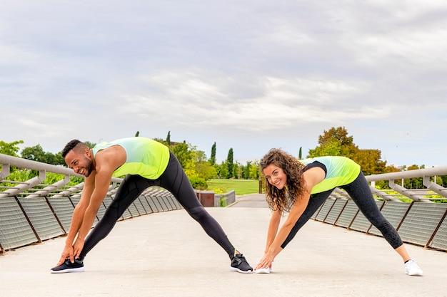 Casal de homem negro e mulher branca faz exercícios de alongamento nas pernas no parque em uma ponte, eles estão agachados com as pernas abertas