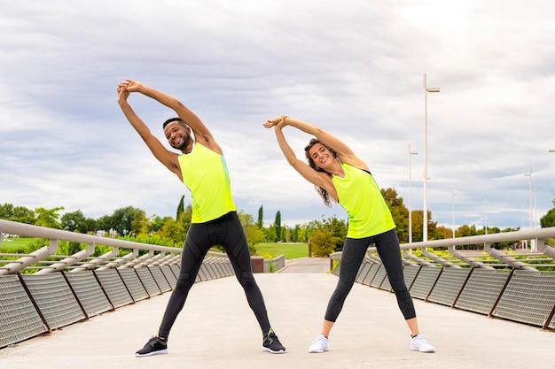 Casal de homem negro e mulher branca, vestida com roupas esportivas, faz exercícios de alongamento ao ar livre