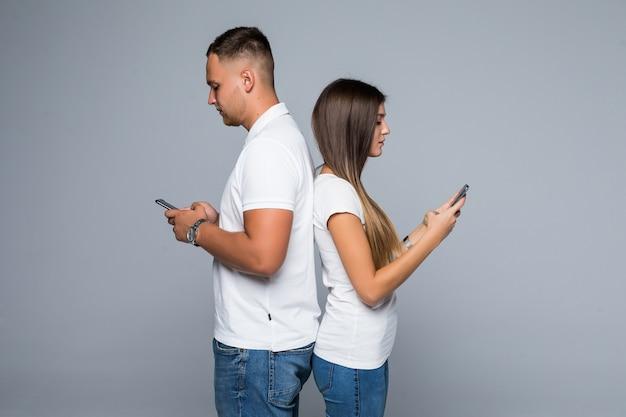 Casal de homens e mulheres em pé com telefones celulares de marca nas mãos, isolados em um fundo cinza
