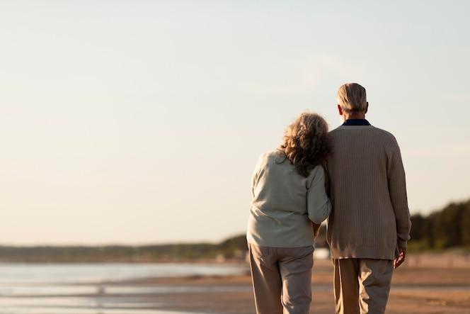 Casal de idosos à beira-mar, tiro médio