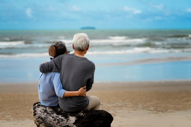 Casal de idosos abraçados à beira-mar