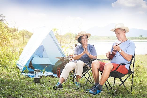 Casal de idosos acampar em uma floresta à beira do rio. ambos se sentam em uma cadeira e tocam música. vida feliz na aposentadoria. conceitos da comunidade sênior