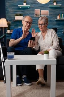 Casal de idosos acenando para uma webcam de videochamada usando smartphone