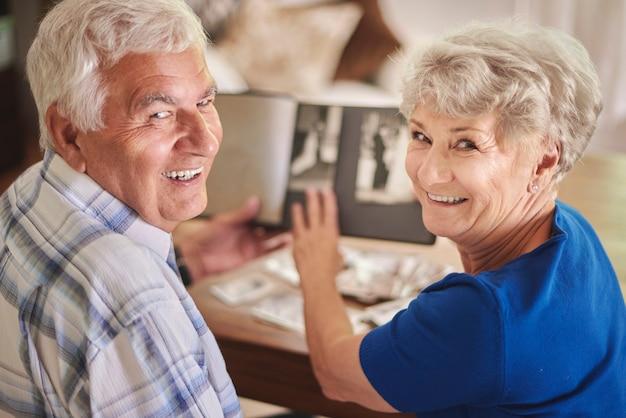 Casal de idosos alegres navegando no álbum com suas fotos