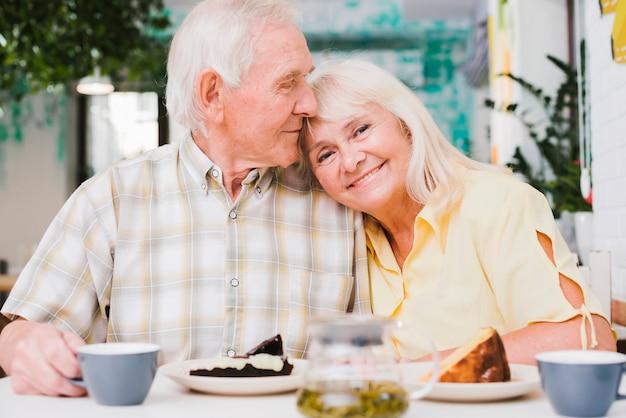 Casal de idosos amorosos bebendo chá com bolo