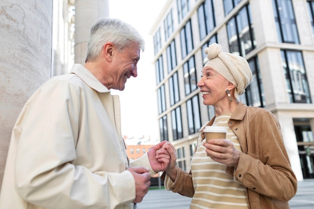Casal de idosos ao ar livre na cidade com uma xícara de café
