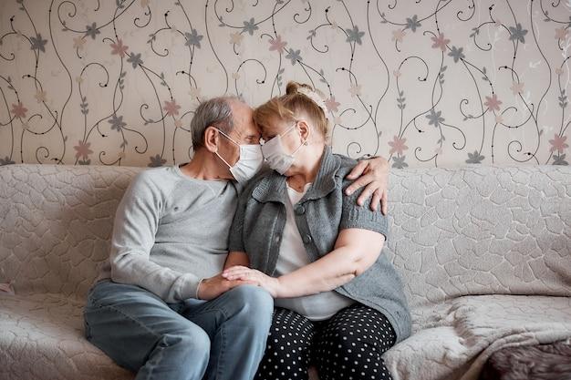 Casal de idosos apaixonados em máscaras médicas em casa em quarentena, valores familiares