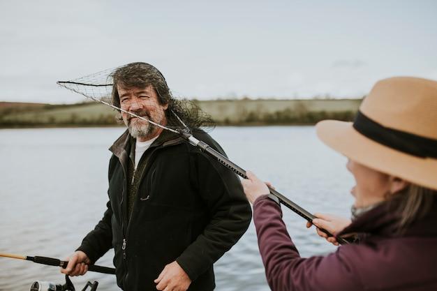 Casal de idosos aposentados aproveitando a atividade de lazer para pescar