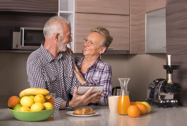Casal de idosos aposentados assistindo a um vídeo juntos em um tablet em uma cozinha