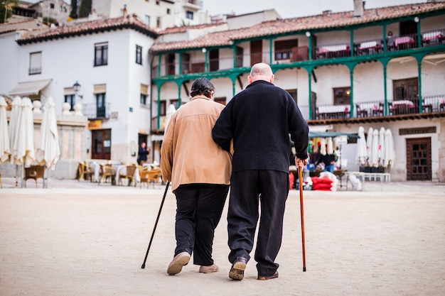 Casal de idosos aposentados caminhando juntos. homem e mulher idosos viajam para chinchon na espanha com amor