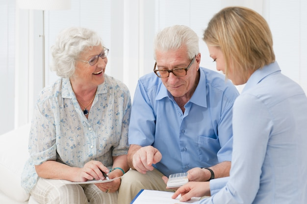 Casal de idosos aposentados planejando seus investimentos com um consultor financeiro