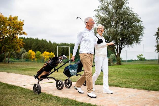 Casal de idosos aproveitando o tempo livre na aposentadoria, jogando golfe e caminhando para o campo de treino