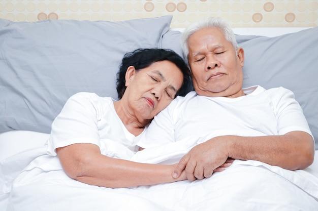 Casal de idosos asiáticos dormir na cama, no quarto.