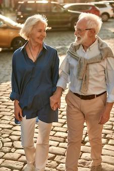 Casal de idosos ativos no fim de semana de mãos dadas e olhando um para o outro com um sorriso no rosto
