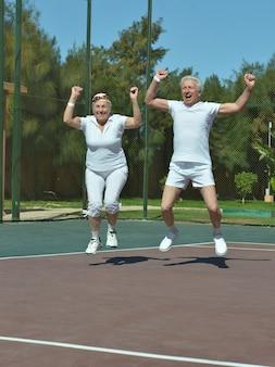 Casal de idosos ativos, vencedores do jogo de tênis