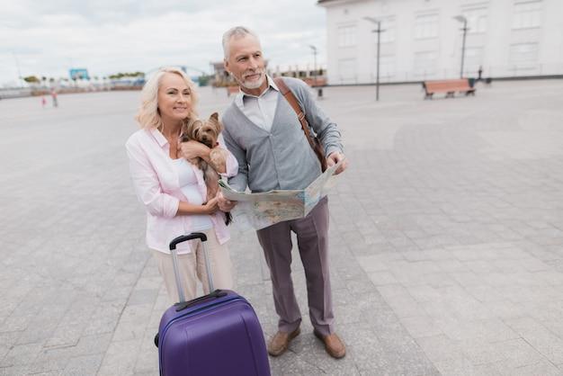 Casal de idosos caminha ao longo do aterro com seu cachorrinho