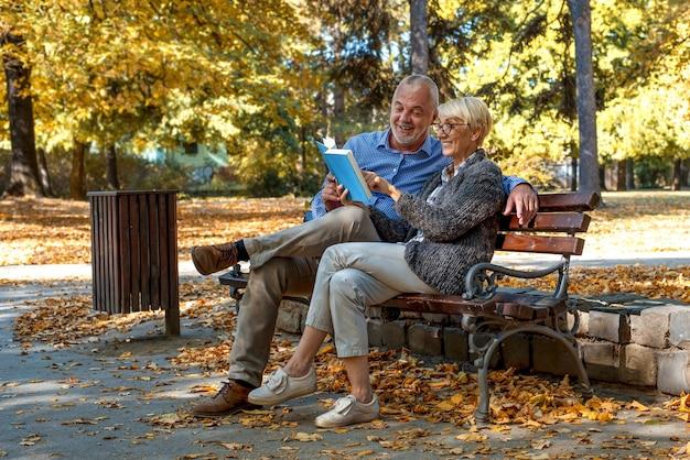 Casal de idosos caucasianos, sentado em um banco e lendo um livro no parque