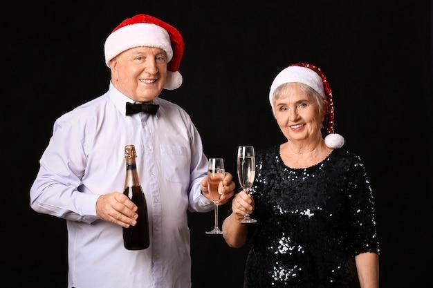 Casal de idosos com champanhe comemorando o natal em fundo escuro